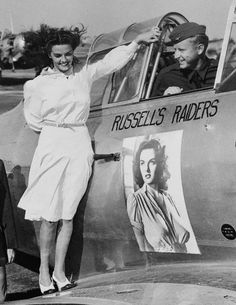 "July 13th, 1941, Stockton, CA — Motion picture beauty Jane Russell inspects her own insignia on the training plane of Don Brown, son of gap-mouthed screen comic Joe E. Brown at the Air Corps Advanced Training School at Stockton. She's the first actress to be chosen mascot by a group of Uncle Sam's airmen. ""D"" flight, 1st Echelon, 2nd section, named their group after the starlet. © Bettmann/CORBIS"