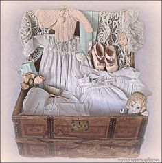 antique doll trunk filled with clothing and accessories.