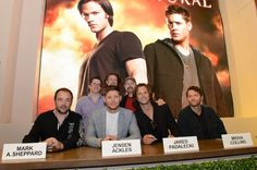 The stars and producers of SUPERNATURAL sign for fans at the Warner Bros. booth at Comic-Con 2012; front, from left: Mark A. Sheppard, Jensen Ackles, Jared Padalecki and Misha Collins; back, from left: Jeremy Carver, Ben Edlund and Jim Beaver (© WBEI. All Rights Reserved.)