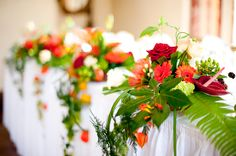 Autumn orange & red head table cascading wedding reception flowers with palm fronds www.anushe.com