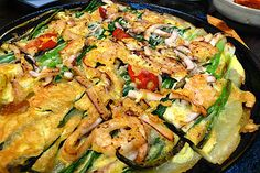 """Pajeon is a type of pancake made from Welsh onions in a wheat-flour batter and fried in oil. Seafood is called """"haemul"""" in Korean, so these pancakes are also referred to as haemul pajeon. Pajeon is the best side dish of Makgeolli (Raw rice wine, Korean traditional fermented alcohol)"""