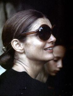 e7038144ad Jackie Kennedy s Pulled back bun  amp  signature sunglasses. Lee Radziwill