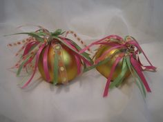"Set of two, 2.5"" diameter pale gold, matte finish bulbs. Adorned in a spray of pink, green, and dotted orange/yellow ribbons. Festive for your tree!  $5.00"