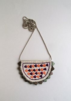 This long necklace has a hand embroidered pendant with a plum, purple and peach geometric arrow design. It is hand stitched on bright cream muslin with a sturdy cream felt backing and small glass Czech geometric triangle beads surrounding it. I have attached the pendant directly to a silver ball chain on the top. The pendant is 3 inches across and 2 1/4 inches long. This is a long necklace measuring at 27 inches long, it can be slipped right over your head but it does have a ball chain…