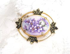 Lovely Ceramic Brooch that has been Hand Painted with Purple Lavender White Flowers surrounded by Gold tone Filigree. On front of the Brooch