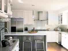 A gray peninsula with waterfall-style quartz countertop provides seating space for three sleek lucite stools while partially dividing the kitchen into separate prep zones.