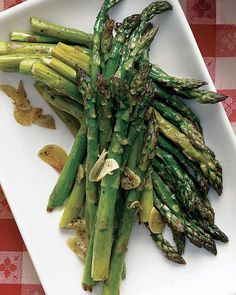 GARLICKY ROASTED ASPARAGUS ~  Ingredients      2 pounds asparagus, trimmed      2 tablespoons olive oil      4 garlic cloves, thinly sliced      Coarse salt and ground pepper    Directions        Preheat oven to 400 degrees. On a large rimmed baking sheet, toss asparagus with oil and garlic; season with salt and pepper. Roast until tender and browned in spots, 15 to 18 minutes. Serve warm or at room temperature ♥  I LOVE THIS STUFF!