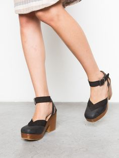 Platform wooden clog with a chunky heel and made with fine leather and features a square toe with strappy detailing around the ankles. Finished with a reptile inspired detailing and a buckle closure.