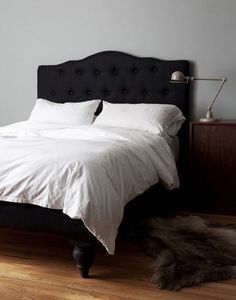 Black upholstered headboard, fur rug, brass bedside lamp, so roar.