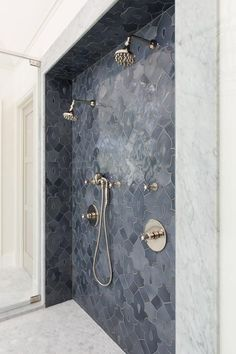 Chic walk in shower features an accent wall clad in gray mosaic fleur de lis mosaic tiles lined with his and hers shower heads alongside a white marble hex tile shower floor.