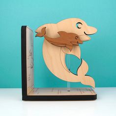 Every child loves dolphins! Our wood Dolphin bookend is super cute in a modern ocean baby nursery or kids room. Our wooden bookend mama & baby dolphin is our original design handcrafted by our family.  What makes our Sea Life Collection of bookends really special is that each sea creature is mounted on a clear acrylic pole so they can rotate around. With this completely unique design, one bookend can be a left or right side by simply spinning the subject around. You can even angle them if...