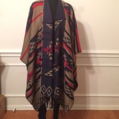 Cape Reversible wrap with Aztec print. The colors are navy, khaki, and rusty red. It's 100% acrylic. Accessories Scarves & Wraps