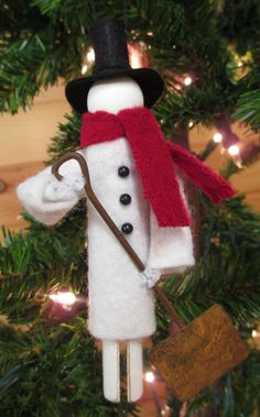 These handmade snowmen are created from a clothespin, wood ball, pipe cleaner and scraps of wool and wool felt. A loop of heavy black embroidery
