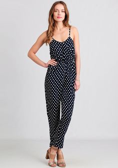 Charming and breezy, this navy blue romper is adorned with charming white polka dots allover and a surplice neckline with side pockets