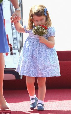 The youngster appeared delighted with her posy and even gave it a discerning sniff...Adorable photo of Charlotte smelling a bouquet on her arrival in Germany July 19 2017