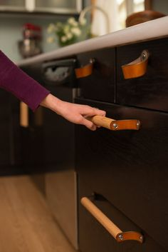 Handmade leather and wood handles add an organic touch to kitchen cabinetry.