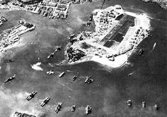 The U.S. Fleet stationed at Pearl Harbor approximately one month prior to the Japanese attack. An aircraft carrier is also visible at the top of the row of battleships (left side of Ford Island in this photo). Thees carriers were away during the actual attack. US Navy photo.