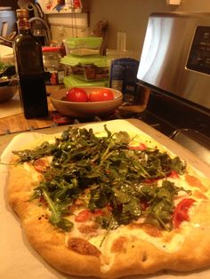 Rocket Pizza - Crisp Homemade crust topped with fresh tomatoes, cheese, and a little arugula salad!