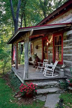 I just love the look of this cabin with the barn red windows and doors and the porch with the rocking chairs!
