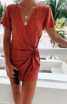 A lightweight woven wrap mini dress with flirty sleeves and a plunging neckline. Grab this rusty rose sundress and beat the heat this summer. Wear over a swimsuit, pair with black cat-eye sunglasses and gold coin necklaces for a cute spring break outfit. #lovelulus