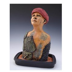 Seed Collector in Red Hat by Katherine Mathisen.  The surface of this clay figure is decorated with germinating seeds and leaves. This piece is inspired by Soviet botanist Nikolai Vavilov.