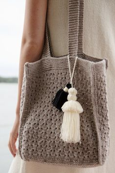 Your beach companion this summer, this woollen bag features a simple yet beautiful lace pattern, and a couple of tassels in contrasting colours for extra elegance. Aran Knitting Patterns, Cable Knitting, Christmas Knitting Patterns, Knitting Stitches, Knit Patterns, Free Knitting, Knitted Bags, Knit Bag, Knitting Accessories