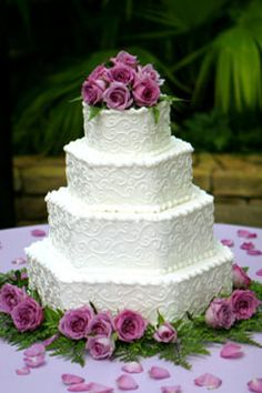 Four tier hexagon shaped buttercream wedding cake, decorated with white buttercream scroll work and pink roses.