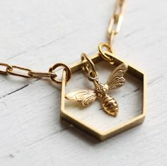 """This necklace features a single vintage brass hexagon to make a honeycomb, with a little bee charm inside. The honeycomb pendant measures 19mm (under one inche) across and the bee is just 10mm long. The necklace chain is 17"""" long and is designed to sit on the collar bone."""