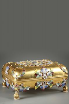 Sizeable gilt bronze and champleve enamel casket with its key, resting on four ball-shaped feet. The entire surface of the box and lid is engraved with champleve crowns, acanthus leaves, and multic...
