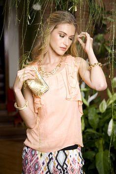Roupas com cores discretas também ficam lindas com bijuterias douradas. Use uma bolsa de paetê para completar o visual.