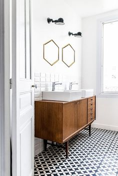 Retro bathroom with printed tile. black sconces, and hexagon shaped mirrors