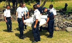 Police and gendarmes carry a piece of debris from an unidentified aircraft found in the coastal area of Saint-Andre de la Reunion, in the east of the French Indian Ocean island of La Reunion, on July 29, 2015.