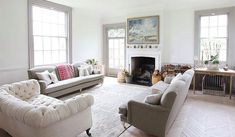 Living room with herringbone wood floor, dueling sofas, a white upholstered sofa with nail head details, a white fireplace and large windows