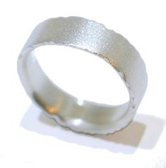 Featuring crumpled and textured edges resembling a leaf this sterling silver ring has an elegant satin finish that almost glitters rather than a mirrored polish, this suits the organic simplicity of the design and delicately sits on the finger.  A perfect unusual and contemporary wedding ring.