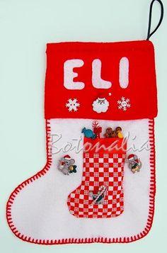 Calcetín navideño hecho en fieltro con nombre en alicación también en fieltro y montones de botoens decorativos del mismo tema. Hay unos ratoncitos navideños que están intentando llevarse los regalos de Eli del calcetín, lleno de caramelos y galletas todos botones. En el Blog de Botonalia.com