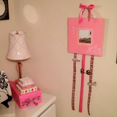 DIY Bow Holder- Ikea mirror customized with paint and ribbon. Perfect for a baby girl's nursery!