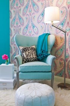 A vintage wingback chair and paired it with a white pouf, creating a cozy reading nook in one corner of the room