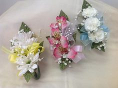 Child's corsages one with all alstroemeria lilys, one with all white dasiys pomps and one with all mini carnations and a touch of baby's breath.