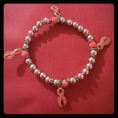 """Breast cancer bracelet Breast cancer bracelet with ribbon charms. Comes from a smoke/pet free home. Measures approximately 2 & 1/2"""" across (outsides of bracelet) Jewelry Bracelets"""