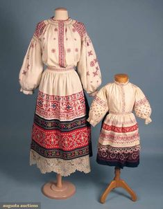 "Mother & daughter regional costume, c. 1900.  Auction listing states ""probably Eastern European""...""w/ detailed embroidered cross-stitch bands in red, blue & white, mother's apron trimmed w/ 'Russian' peasant bobbin lace"""