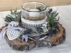 Auf einer geweißten Baumscheibe sitzt der geweißte, mit künstlichem Lavendel und weißen Blüten verzierte Kranz. Viel Naturmaterial, ein weißes Ornamentherz und fliederfarben-gepunktetes Band zieren...