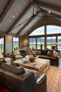 Mountain modern living room with a large hide ottoman, matching sofas, wood beamed ceiling, warm colors, and huge windows.