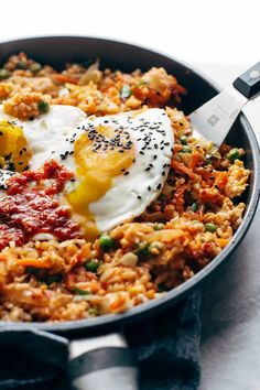 Kimchi Fried Rice FTW! Cauliflower rice, frozen peas and carrots, fresh garlic and ginger, soy sauce, chili paste, a forkful of kimchi, and finished with a runny yolk waterfall. A new kind of comfort food. #kimchi #friedrice #egg #dinner #easyrecipe | pinchofyum.com