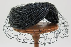 Black plastic tubing hatlet overlaid with black net veiling | Designer: Benjamin B. Green-Field  (Bes-Ben) | United States, 1955 | Formed as an open circular crown, the hatlet is composed of three sections of black tubing shaped as crescents, attached at points | University of North Texas