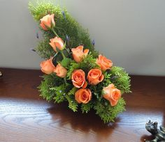 Perfect peach coloured roses with fir foliage.