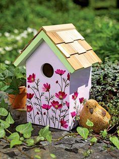 cabane à oiseaux avec des fleurs roses peintes                              …