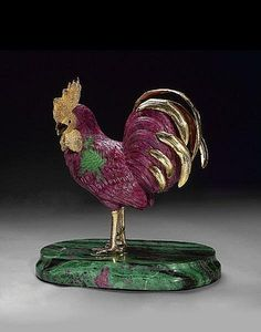 <i></i><i>Designed by Luis Alberto Quispe</i><br />A life-like rendering of a full-grown rooster is convincingly achieved in this carving formed from a single, immense specimen of Tanzanian ruby, <i>with a gross weight of approximately 12.2lbs (27,669 carats)</i>, a difficult feat considering the hardness of the stone. The carving is highlighted with a beak carved of South African tiger's eye quartz, set with garnet cabochon eyes and mounted with 18K yellow gold feet and feathers. The ...