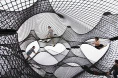 """Net-Blowup-by-Numen-and-ForUse This inflatable installation playspace features a large bulbous shell that contains a series of interwoven nets inside. Guests are welcomed to climb, explore and play within the bright and airy interior, bouncing in an alien """"bouncy castle"""" for adults. The interior nets are attached to different points on the inflatable exterior shell which, when fully inflated, act as structural supports — a sort of elastic suspension system."""