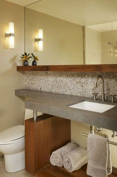 Mirror and counter extended over toilet. Contemporary bathroom by Michael Tauber Architecture