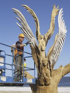 angel chainsaw carvings | chain saw artist dayle lewis applies stain to the carvings of angels ...